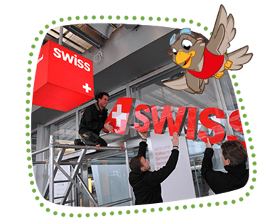 Lexi shows how two men attach the new SWISS logo